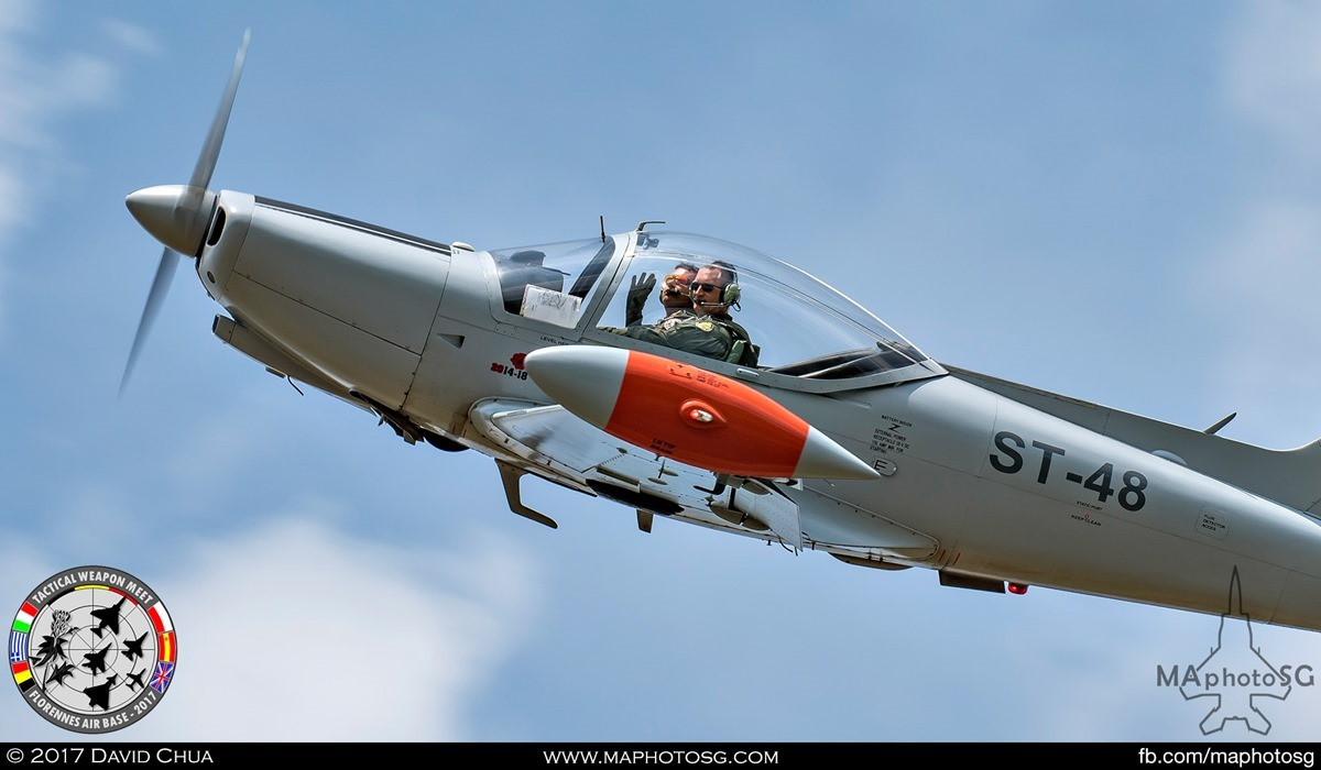 25. Pilots of the Belgian Air Force SF.260 (ST-48) waves crowd as it performs a low pass.