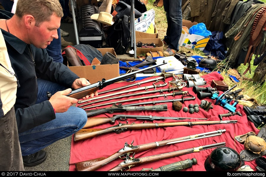 A potential buyer checks out an antique rifle