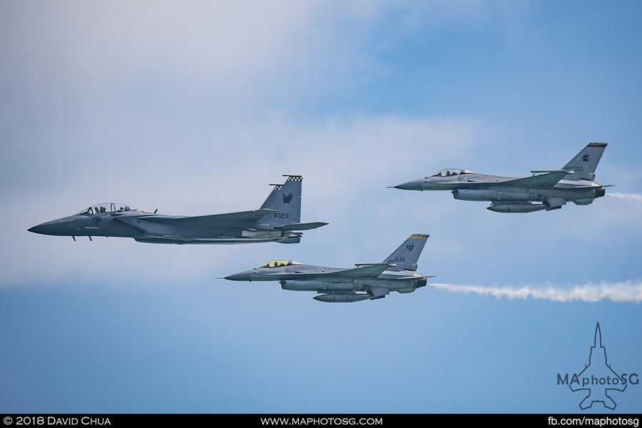 The formation of F-15SG and F-16C enters the show in arrowhead formation from the right trailing smoke