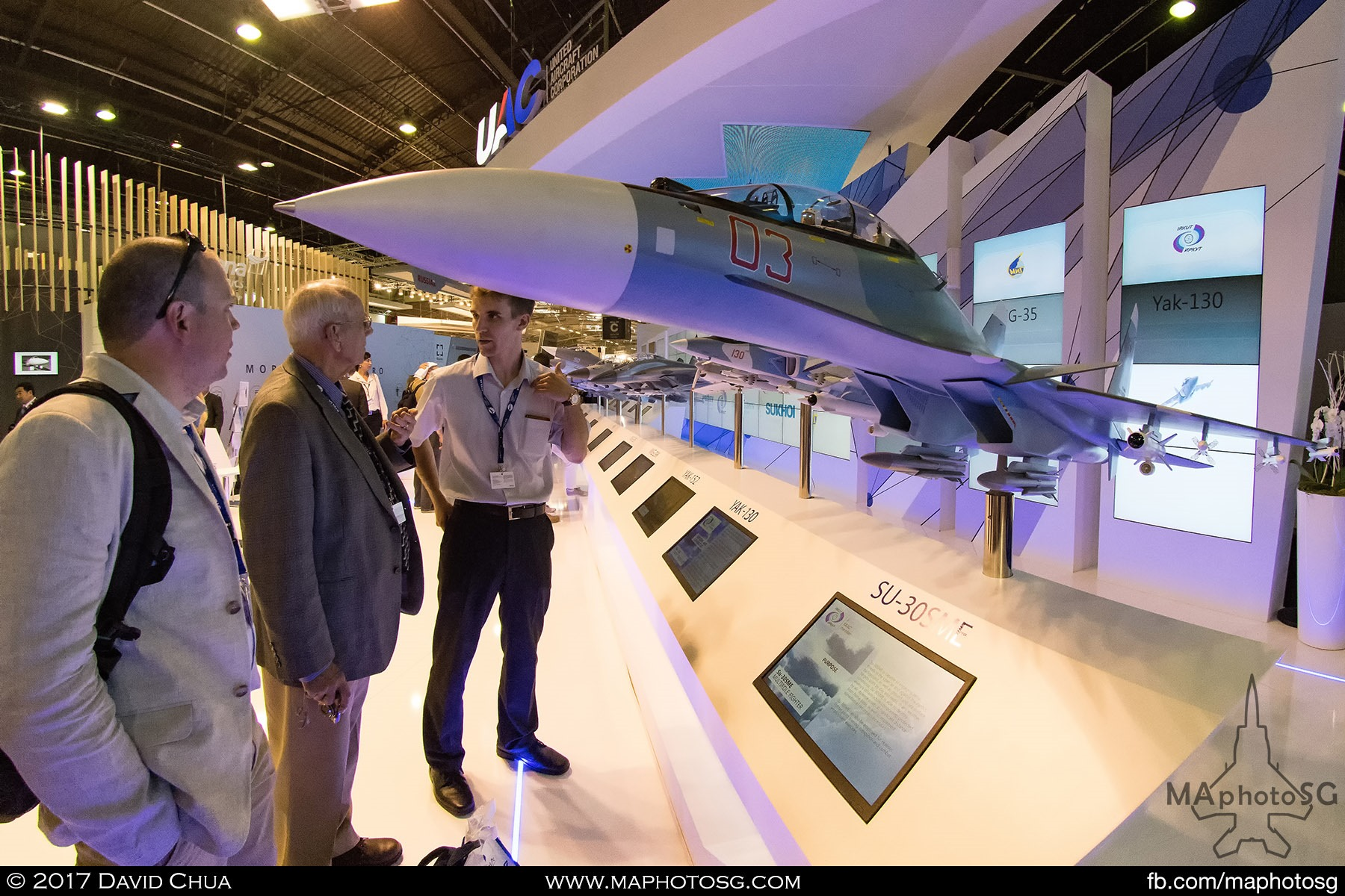 17. A representative from the United Aircraft Corporation explains the details of the SU-30SME to two interested gentlemen.