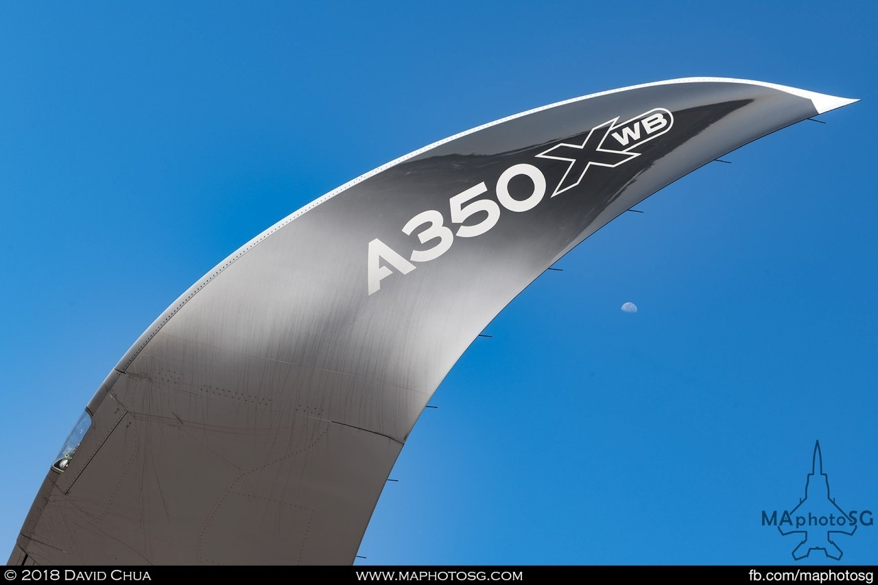 The moon sets under the curved winglet of the Airbus A350-1000