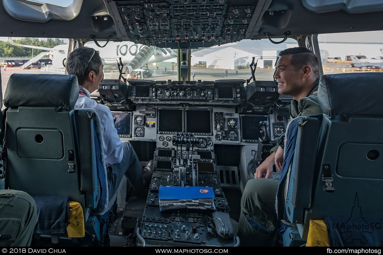 A visitor having a chat with a crew member in the cockpit of the C-17A Globemaster III