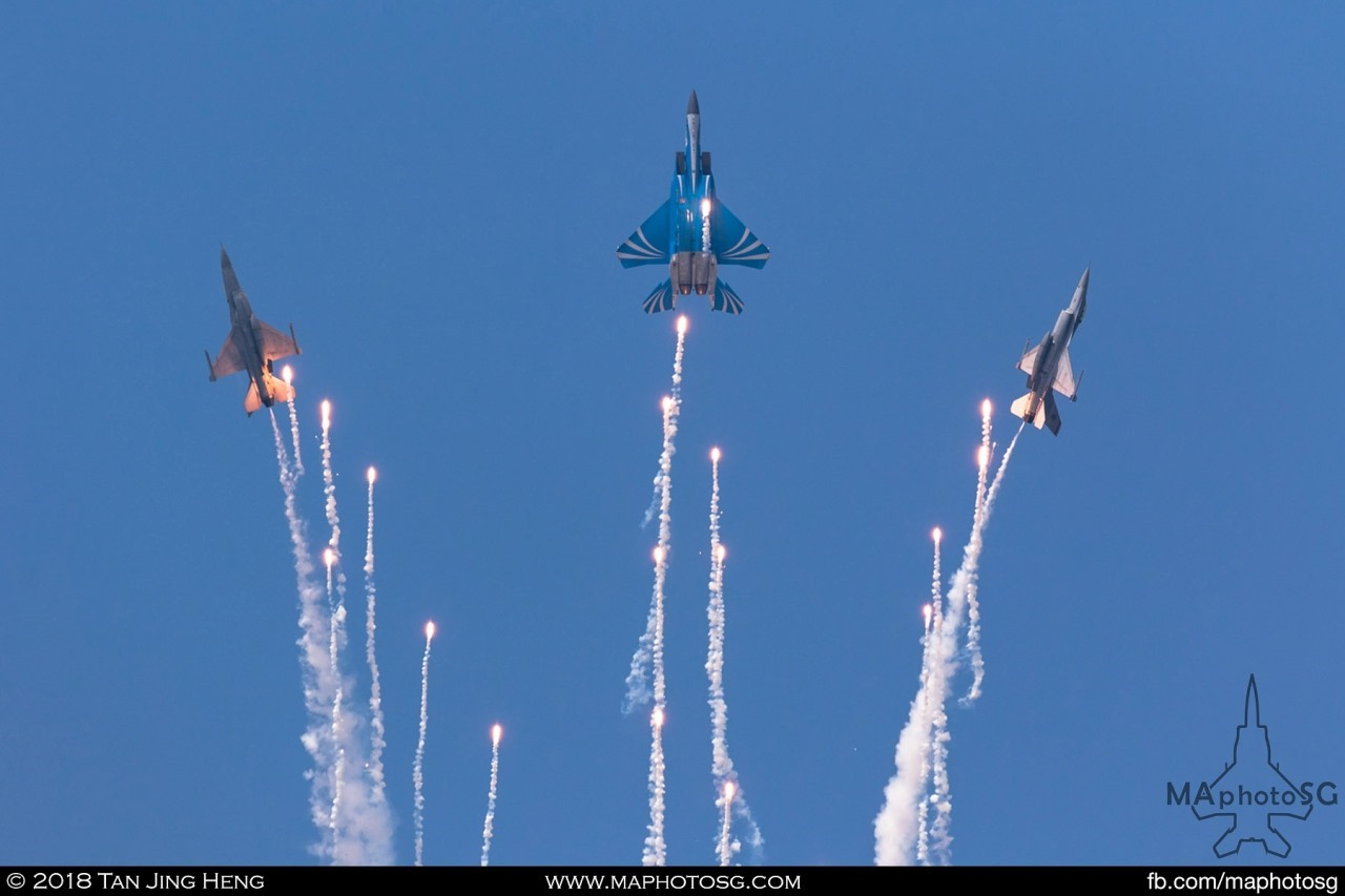 The F-15SG and F-16Cs of the RSAF Aerial Display Team pulls up into vertical and deployed a string of flares in their finale manoeuvre. The Golden Salute.