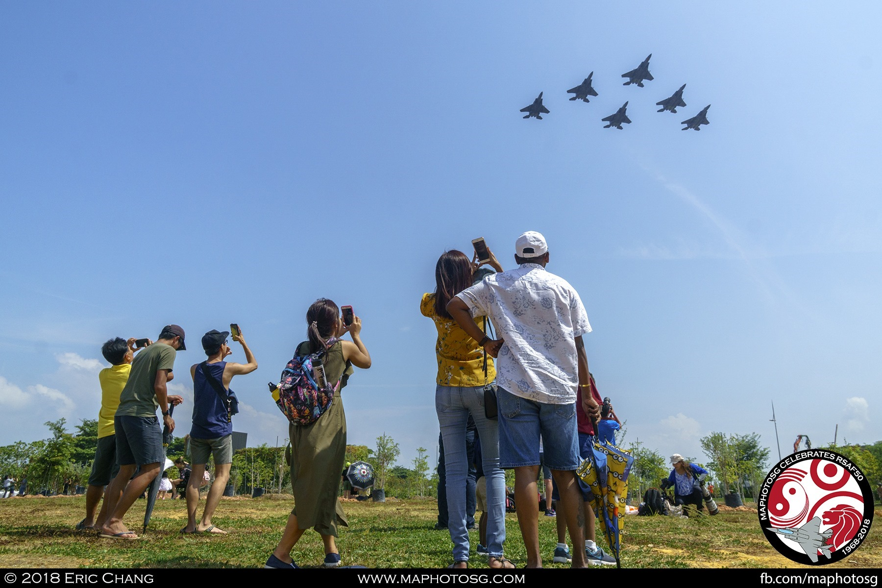 Spectators at the waterfront near Marina Barrage captures the F-15SGs with their mobile phones as the they fly past in Delta Formation.