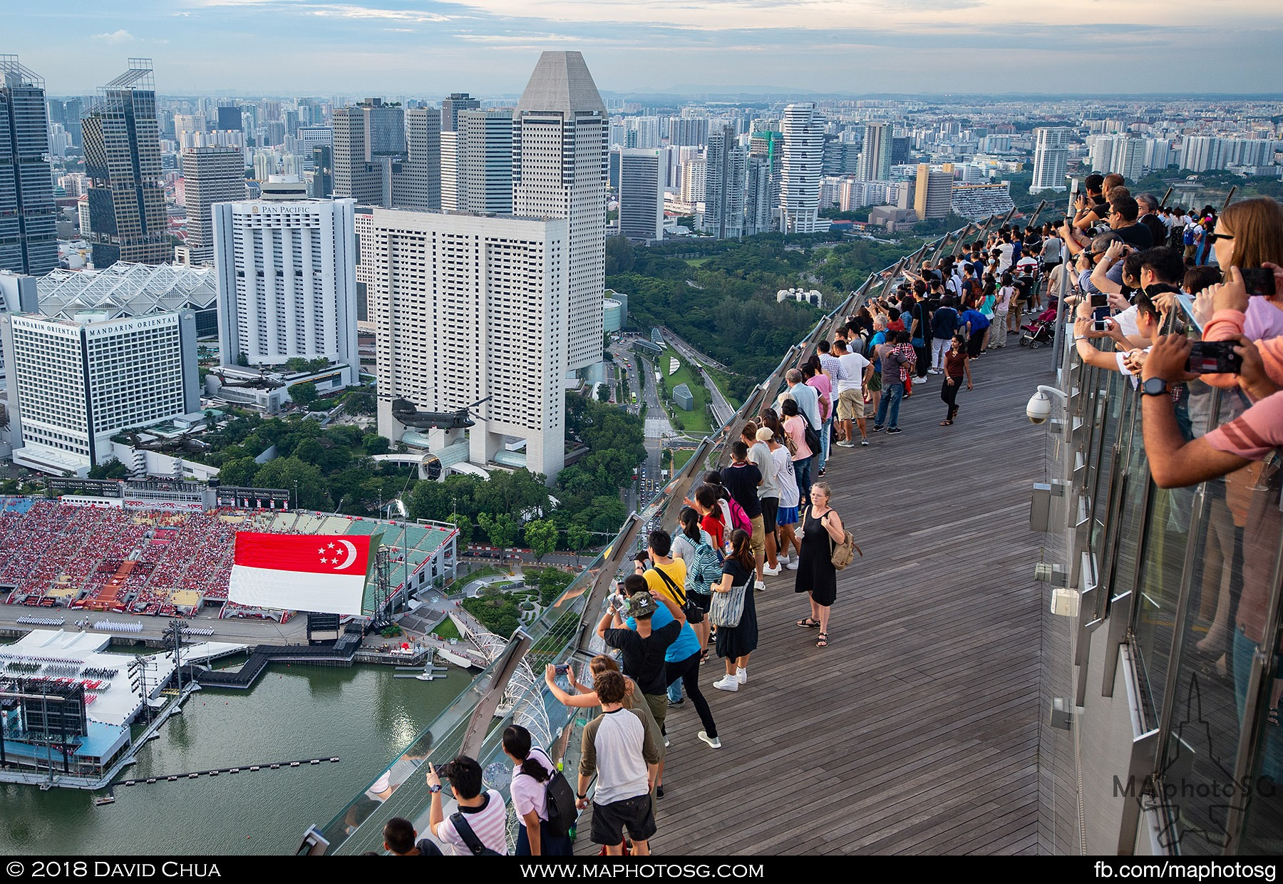 20. Visitors to the Marina Bay Sands Skypark views the state flag fly past from a high angle.