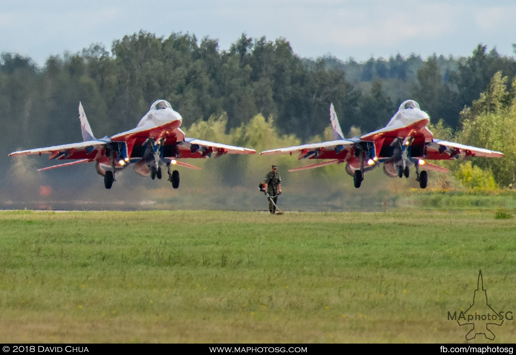 33. A soldier on grass cutting duty as a pair of MiG-29s of the Swifts Aerobatic Team takes off