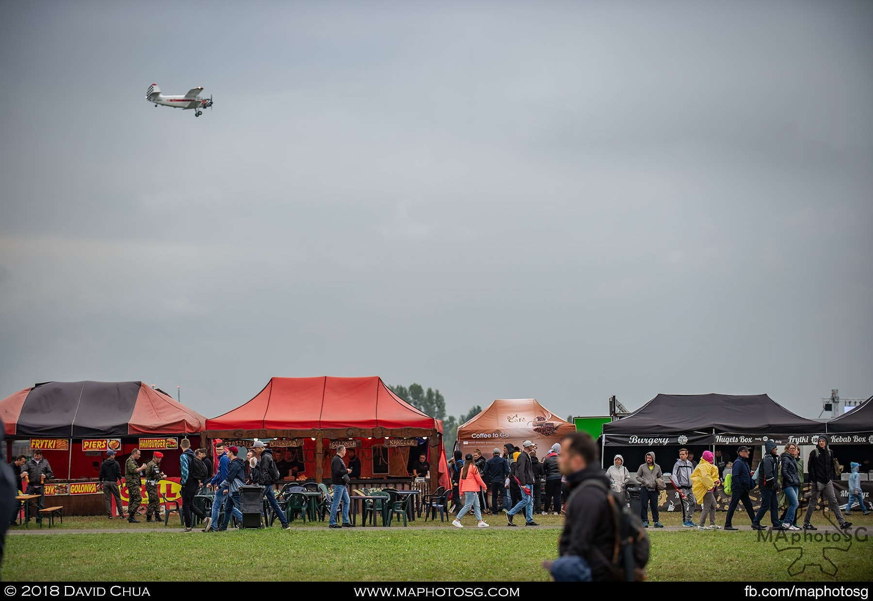 16. Antonov An-2 flies over a row of food kiosks at the Radom Airshow