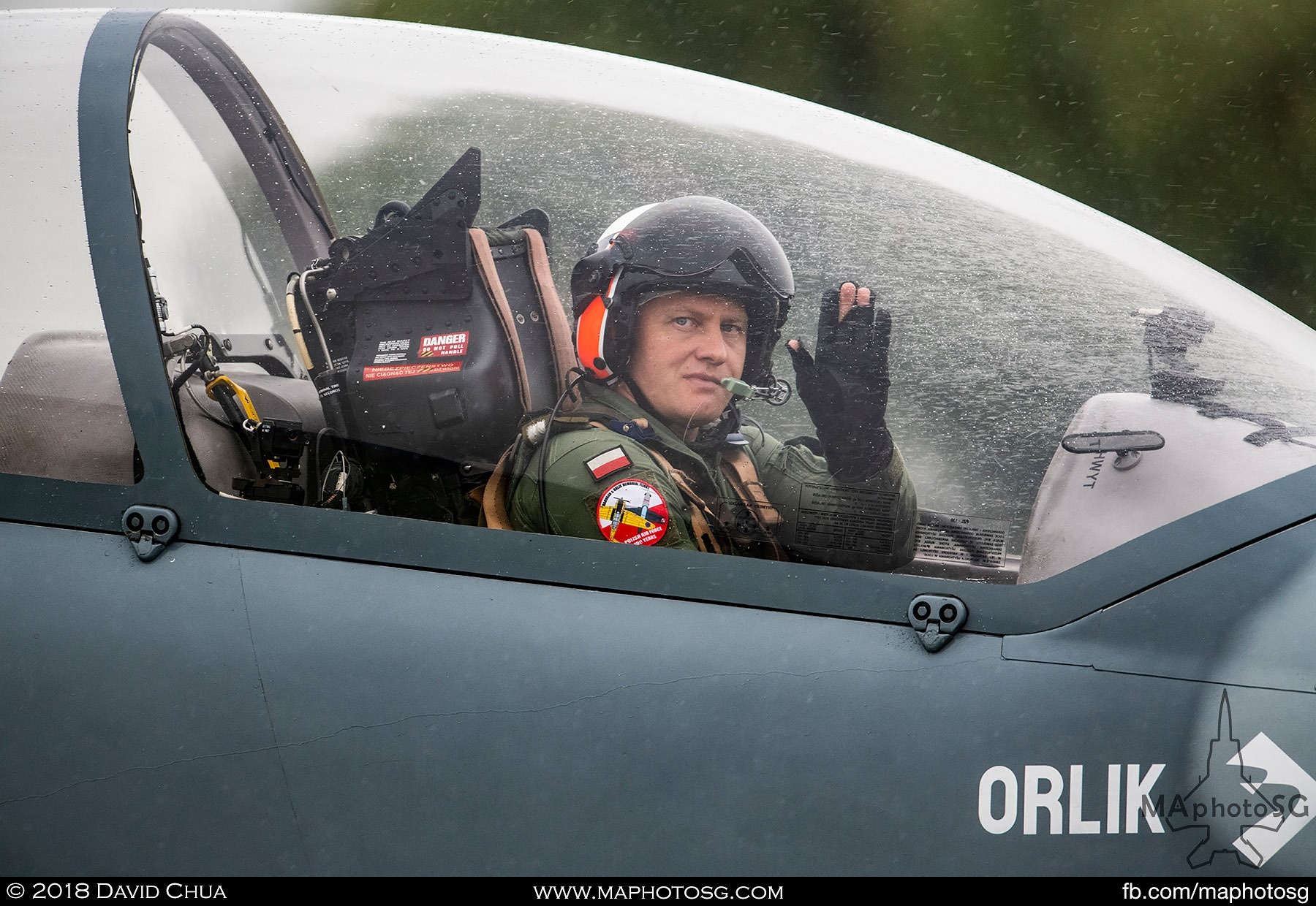 25. Pilot of a Polish Air Force Team Orlik PZL-130 waves as he taxis past the crowd